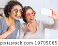 Two sisters are having fun while making selfies.  19705065