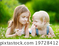 Two cute little sisters laying in the grass 19728412