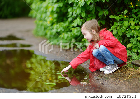 Adorable girl playing in a puddle on rainy day 19728521