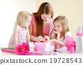 Mother and her two daughters wrapping a gift 19728543