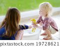 Little girls helping her mom to clean up 19728621