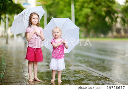 Stock Photo: Two cute little sisters on a rainy summer day