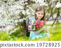 Adorable little girl in blooming cherry garden 19728925