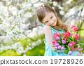 Adorable little girl in blooming cherry garden 19728926