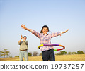 happy kid playing  hula hoops outdoors 19737257