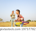 happy little girl playing  hula hoops outdoors 19737782
