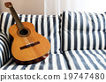 acoustic guitar on a couch 19747480