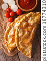 Italian calzone closeup on a paper and ingredients 19774310