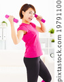 happy young woman exercising with dumbbells in living room 19791100