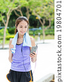 Sporty girl look at the mobile phone after running 19804701