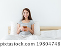 Asian woman holding a cup of tea and sitting on bed 19804748