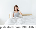 Woman feeling headache and sitting on the bed 19804863