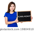 Young woman with blackboard showing a word scholarship 19804910