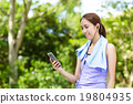 Sporty woman look at the cellphone with earphone 19804935