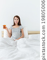 Woman holding a glass of tea and sitting on bed 19805006
