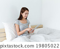 Woman use of tablet and lying on the bed 19805022