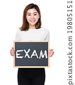 Young woman with the blackboard showing a word exam 19805151
