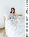 Young woman feeling unwell on bed 19805598