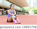 Sporty Woman listen to music ans sitting on sport arena 19805708