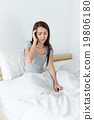 Woman got headache and sitting on bed 19806180