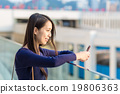 Happy woman using a smart phone in the street 19806363