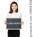 Young woman with of blackboard showing a word scholarship 19806368