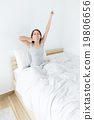 Young woman yawning on the bed 19806656