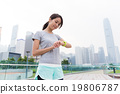 Asian Woman look at the sport watch after running 19806787