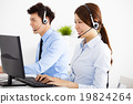 smiling business man and woman with headset working in office 19824264