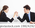 Business man and woman arm wrestling on desk in office 19824292