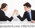 Business man and woman arm wrestling on desk in office 19824294