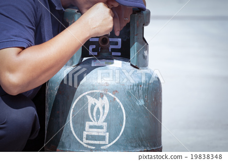 Cigarette in hand near gas tank cylinder  19838348