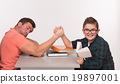Young man and his son arm wrestling 19897001