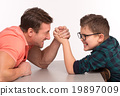 Young man and his son arm wrestling 19897009