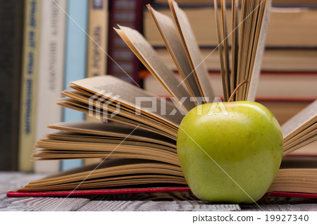 Stock Photo: Open book, hardback books and green apple on