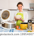 Woman cooking with multicooker at home. 19954007