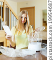 girl reading user manual for new electric steamer 19954687
