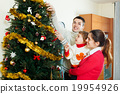 parents and girl decorating Christmas tree 19954926