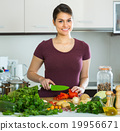 Woman with vegetables at kitchen table . 19956671
