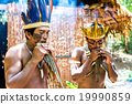 Native Brazilian men playing wooden flute 19990859