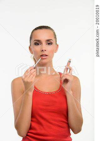 Sensual woman applying gloss on her lips. 20010019