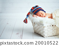 Cute newborn baby in blue knit cap sleeping in basket 20010522