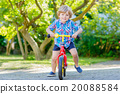 kid boy driving tricycle or bicycle in garden 20088584