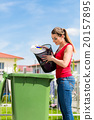 Woman throwing waste paper away in container 20157895