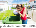 Woman throwing waste paper away in container 20157896
