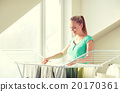 happy woman hanging clothes on dryer at home 20170361