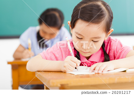 Stock Photo: children in classroom with pen in hand