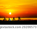 Silhouettes of childrens on bicycle against sunset 20206573
