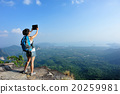 young woman hiker taking photo with digital tablet on mountain peak 20259981