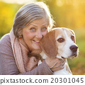 Active senior woman hugs dog 20301045
